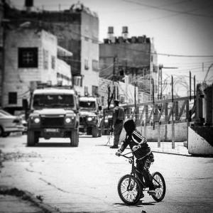 A__Palestinian_boy_on_a__bike_watches_as_thre