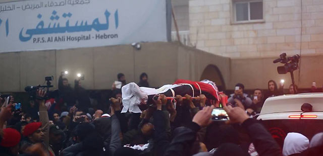 Finally returned. The seventeen bodies arrive one at a time in seventeen separate ambulances. Hundreds of Palestinians stand in solidarity with the families as each body is lifted and carried above the crowd.